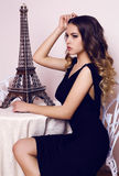 Beautiful young woman with luxurious curly hair in elegant black dress Stock Photography