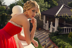 Beautiful young woman in luxurious red dress Stock Photo