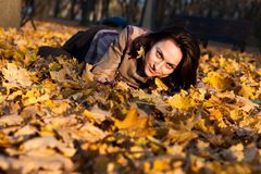 Beautiful young woman lying in autumn leaves Stock Photography