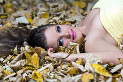 Beautiful young woman lying autumn leaves Royalty Free Stock Photography