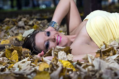 Beautiful young woman lying autumn leaves Stock Photos