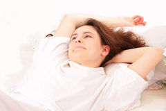 Beautiful young woman lying in bed Stock Photos