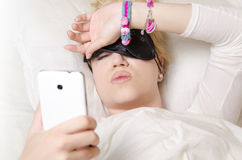 Beautiful young woman lying in bed and cant sleep. Pretty girl lying in bed pulling up sleeping mask to see what time is it/ wake up, or cant sleep concept Stock Photography