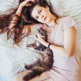 Beautiful woman lying in bed with her charming cat royalty free stock image