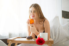 Beautiful young woman lying in bed and holding orange Stock Images