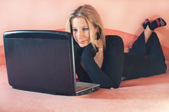 Beautiful young woman lying on bed with laptop Stock Image