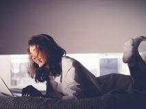 Beautiful young woman lying on the bed with notebook Stock Photo
