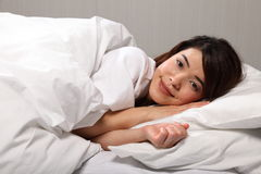 Beautiful young woman lying in bed smiling Royalty Free Stock Photography