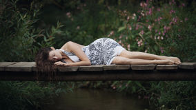 Beautiful young woman lying on the bridge over the forest river. stock photos
