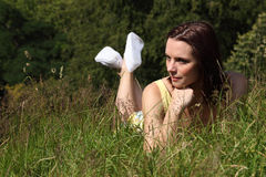 Beautiful young woman lying in countryside grass Royalty Free Stock Photo