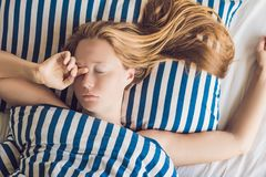 Beautiful young woman lying down in bed and sleeping. Do not get enough sleep concept.  stock image