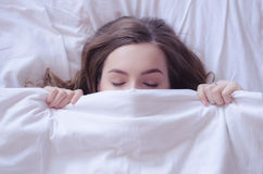 Beautiful young woman lying down in bed and sleeping Royalty Free Stock Photography