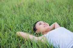 Beautiful young woman lying down in green grass meadows. Beautiful young woman lying down in green grass meadows background Stock Image