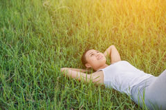 Beautiful young woman lying down in green grass meadows. Stock Image