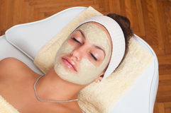 Beautiful young woman lying with facial mask Stock Images
