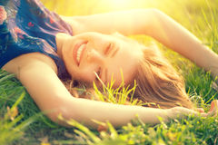 Beautiful young woman lying on the field Stock Image