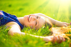 Beautiful young woman lying on the field Stock Photography