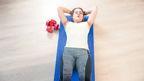 Beautiful young woman lying on fitness mat and doing abs sit-ups. Beautiful woman lying on fitness mat and doing abs sit-ups Royalty Free Stock Images
