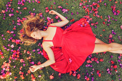 Beautiful Young Woman Lying in Flowers. Beautiful Young Woman Lying on Grass with Flowers In Red Dress Royalty Free Stock Images