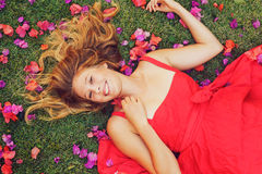 Beautiful Young Woman Lying in Flowers. Beautiful Young Woman Lying on Grass with Flowers In Red Dress Royalty Free Stock Image