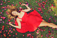 Beautiful Young Woman Lying in Flowers. Beautiful Young Woman Lying on Grass with Flowers In Red Dress Stock Image
