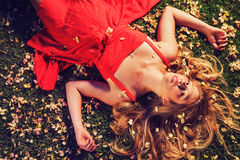 Beautiful Young Woman Lying in Flowers. Beautiful Young Woman Lying on Grass with Flowers In Red Dress Stock Photography