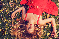 Beautiful Young Woman Lying in Flowers. Beautiful Young Woman Lying on Grass with Flowers In Red Dress Royalty Free Stock Photography