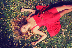 Beautiful Young Woman Lying in Flowers. Beautiful Young Woman Lying on Grass with Flowers In Red Dress Stock Photos