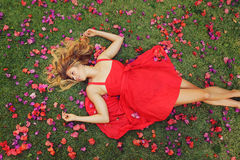Beautiful Young Woman Lying in Flowers. Beautiful Young Woman Lying on Grass with Flowers In Red Dress Royalty Free Stock Photos