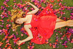 Beautiful Young Woman Lying in Flowers. Beautiful Young Woman Lying on Grass with Flowers Royalty Free Stock Images