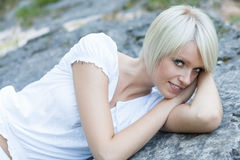 Beautiful young woman lying on a granite rock. Beautiful young woman with short trendy blond hair lying on a granite rock peering up a the camera with a friendly Royalty Free Stock Photos