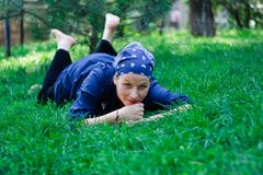 Beautiful young woman lying in the grass. Green-eyed beautiful young woman dressed in blue and with a bandanna lying in the grass Stock Image