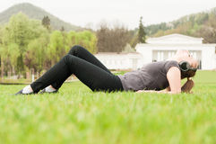 Beautiful young woman lying on grass and listening music Stock Image