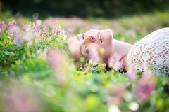 Beautiful young woman lying on grass with spring flowers Stock Photography