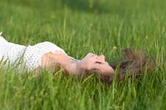 Beautiful Young Woman lying on the green grass Royalty Free Stock Image