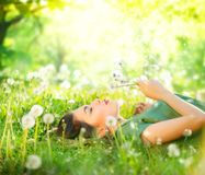 Beautiful young woman lying on green grass and blowing dandelions Royalty Free Stock Photos