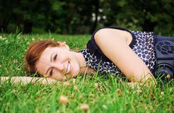 Beautiful young woman lying on green grass outdoor. Royalty Free Stock Photography