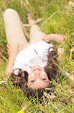 Beautiful young woman lying on green grass Stock Photos