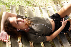 Beautiful young woman lying on hammock with mobile phone. Portrait of a beautiful young woman lying on hammock with mobile phone Royalty Free Stock Photos