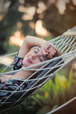 Beautiful young woman lying in a hammock and relaxing with close. D eyes Royalty Free Stock Photos