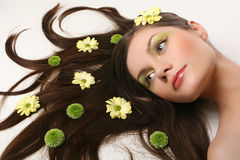 Beautiful young woman lying on isolated background. Beautiful young woman lying on isolated white background with flowing hair and flowers Stock Photos