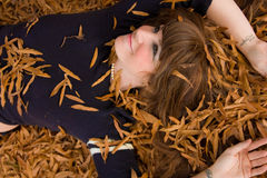 Beautiful Young Woman Lying in Leaves. A portrait of a gorgeous young woman in leaves, with a tattoo on her wrist that says Imagine Stock Photography