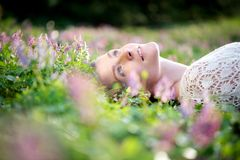 Beautiful young woman lying in meadow of flowers Stock Images