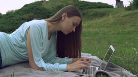 A beautiful young woman is lying ouside and working on a computer. A pretty lady with long brown hair is lying on the blanket on the grass and typing on a stock video