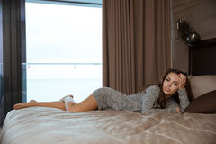 Beautiful young woman lying and relaxing on bed Royalty Free Stock Image