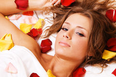 Beautiful young woman lying in rose petals Royalty Free Stock Photo