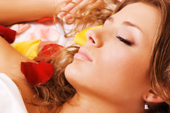 Beautiful young woman lying in rose petals Stock Photo