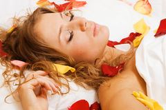 Beautiful young woman lying in rose petals Stock Photography