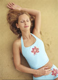 Beautiful young woman lying on the sand Stock Images