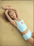 Beautiful young woman lying on the sand Royalty Free Stock Photos